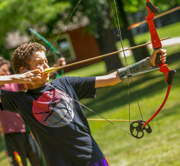 Male camper shooting an archery arrow
