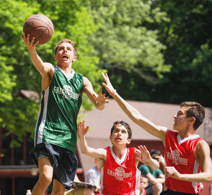 Boys dunking a basketball during a game
