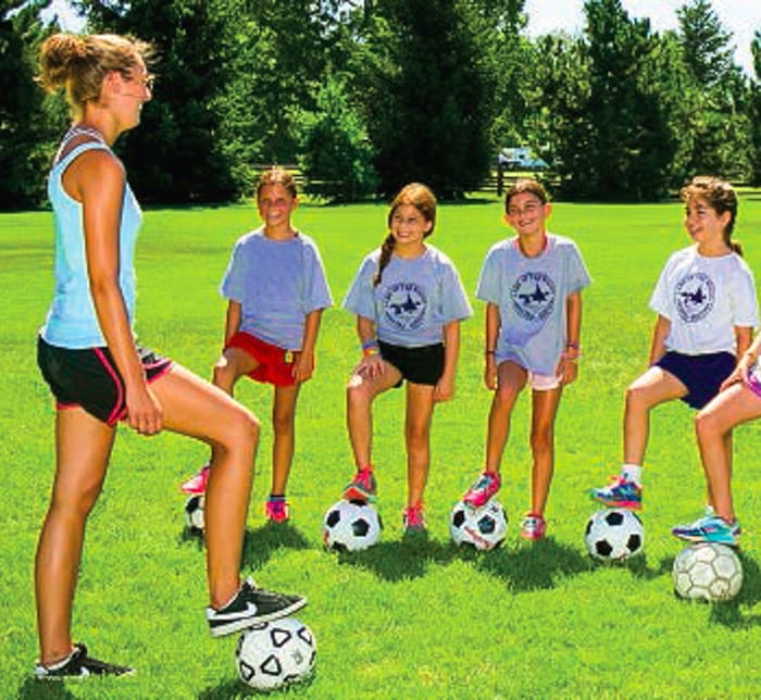 Counselor teaching girls soccer